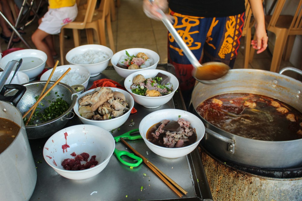 Ladling the bun bo Hue into bowls