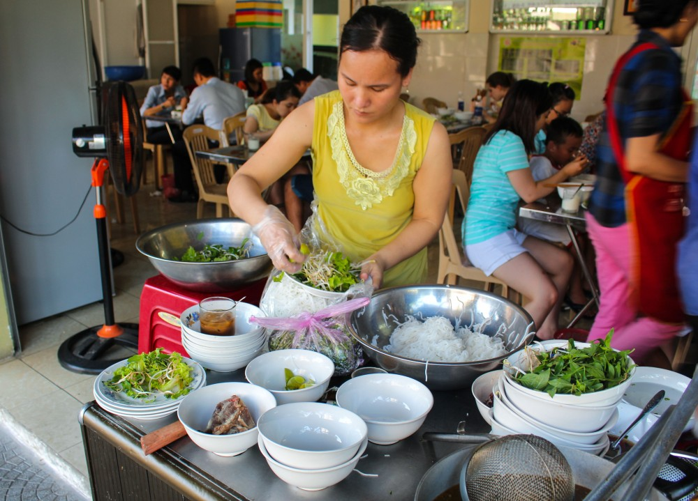 A woman preparing our rau thom to accompany the bun bo Hue